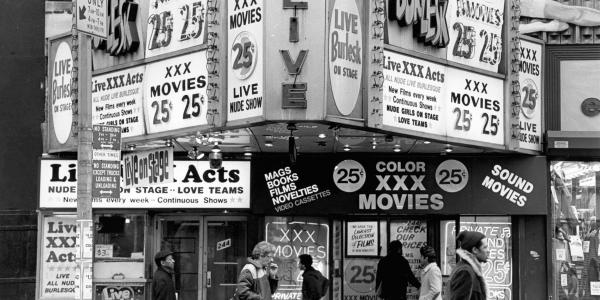 A black and white photo of a theater with multiples signs reading